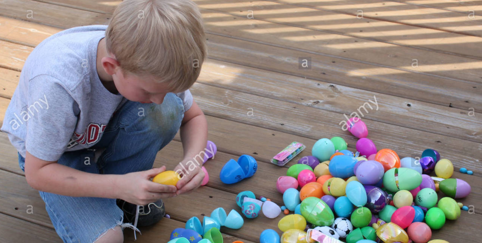A child opens a plastic easter egg, with numerous plastic eggs strewn around beside him.