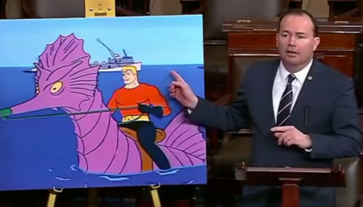 Senator Mike Lee pointing at a picture of Aquaman riding an enormous seahorse