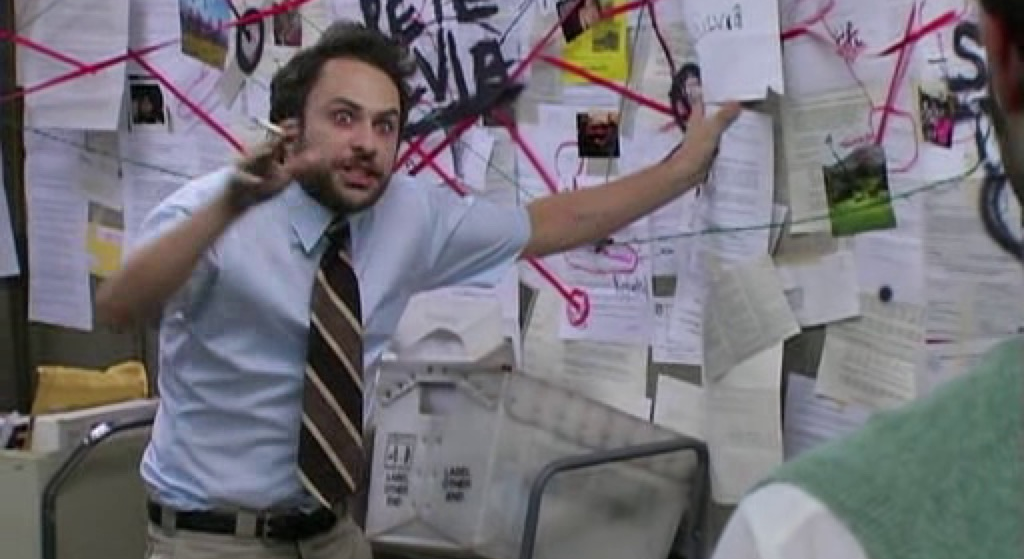 Charlie Reynolds from It's Always Sunny in Philidelphia, looking deranged as he tries to explain the multitude of connections between pieces of paper on a corkboard behind him